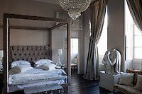 This contemporary bedroom retains a feeling of traditional country house grandeur, with its original wood flooring, floor-to-ceiling curtains and antique furniture