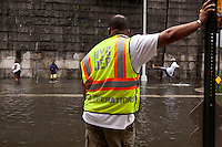 A New York City Department of Environmental Protection employee looks out at a rain water flooded section of 12th Avenue in Hamilton Heights, New York City, NY, USA as people play in the water shortly after tropical storm Irene passed over the city, 28 August 2011.