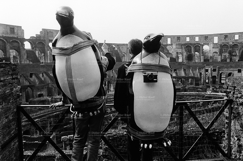 Italy. Lazio region. Rome. The Colosseum. Two tourists carry on their back penguins and photo cameras. The Colosseum, or the Coliseum, originally the Flavian Amphitheatre (Colosseo), is an elliptical amphitheatre in the centre of the city of Rome, the largest ever built in the Roman Empire. It is considered one of the greatest works of Roman architecture and Roman engineering. 10.2.1991 &copy; 1991 Didier Ruef