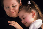 Mother and daughter hugging each other and smiling.   MR