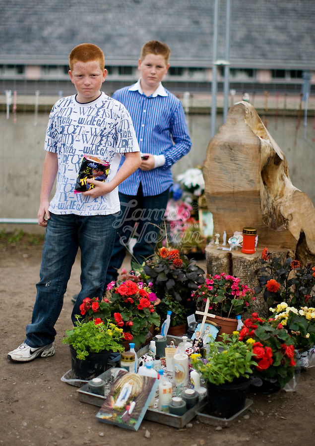 """Pictured at the Holy stump are John and James Quilligan from Limerick. Thousands of Irish Catholics have flocked to a County Limerick church to pray at the stump of a recently cut willow that many observers say has the silhouette of the Virgin Mary. The phenomenon at St Mary's parish church in Rathkeale, population 3,000 or so, harkens back to decades when Catholic devotion and pilgrimages were the dominant feature of rural life in Ireland. Some are tying the fervor for Rathkeale's """"Holy Stump"""" to Ireland's stunning economic decline over the past year. When a willow tree was felled near the church entrance, a worker cut through the stump at a near-vertical angle, revealing a wooden relief that inspires some to see the Virgin Mary. Picture James Horan"""