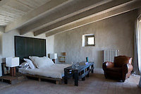 A rustic master bedroom in a Spanish stone house with local terracotta tiled floor and painted beamed ceiling. The room is simply furnished with a platform bed made from salvaged wood with a headboard of metal panels, a bench and leather armchair.