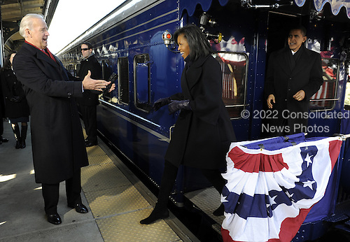 Wilmington, DE - January 17, 2009 -- United States Vice President Joe Biden (L) is greeted by President-elect Barack Obama's wife Michelle as Obama watches on at Wilmington, Delaware, where the Obamas picked up the Bidens, on the Whistle Stop Train Tour, on Saturday, January 17, 2009. The ceremonial trip will carry President-elect Obama, Vice President-elect Biden and their families to Washington for their inaugurations with additional events in Philadelphia, Wilmington and Baltimore. Obama will be sworn in as the 44th President of the United States on January 20, 2009.  .Credit: Kevin Dietsch - Pool via CNP