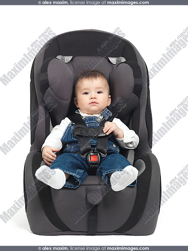 Seven month old baby sitting in a booster seat isolated on white background