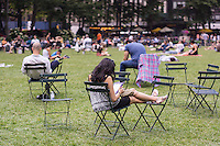 A woman takes advantage of free wi-fi on her tablet computer on the lawn in Bryant Park in New York on Friday, June 27, 2014.  (© Richard B. Levine)