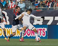 Vancouver Whitecaps FC midfielder Matias Laba (15) attempts to control the ball as New England Revolution midfielder Andy Dorman (12) pressures. In a Major League Soccer (MLS) match, the New England Revolution (blue/white) tied Vancouver Whitecaps FC (white), 0-0, at Gillette Stadium on March 22, 2014.