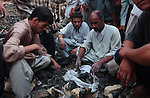 Iraqi men collect human remains at the Tomb of Ali (Imam Ali Mosque), the scene of a massive car bombing that killed at least 70 people, including one of Iraq's most important Shiite clerics, Ayatollah Mohammed Baqir al-Hakim August 29, 2003 in the city of Najaf, Iraq.