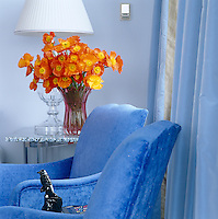 Vivid orange flowers have been carefully chosen and arranged to contrast with the blue walls and furnishings in the living room