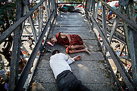A Buddhist monk and other people sleep at the bridge over railway tracks in Yangon's suburbs December 2, 2011. Pro-democracy leader Aung San Suu Kyi welcomed on Friday renewed U.S. engagement with Myanmar, saying she hoped it would set her long-isolated country on the road to democracy.  REUTERS/Damir Sagolj (MYANMAR)