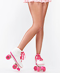 Closeup of sexy long legs of a young woman wearing a pink skirt and classic roller girl derby skates isolated on white background