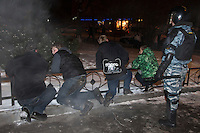 Moscow, Russia, 15/12//2010..Riot police stand guard over youths who tried to block a street near Kievsky railway station, where police detained up 1,000 people during an operation to prevent ethnic riots. There were scuffles as hundreds of riot police were deployed to prevent clashes between Russian nationalists and traders from the Caucasus, many of whom work at a market near the station.