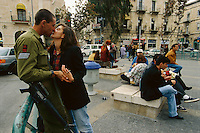 An Israeli soldier catches a kiss while in uniform.