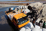 A worker tamping down bags of salt as a turck is loaded at the Ada Songor Salt Project, the largest salt production facility in the vicinity of the Songor Lagoon.