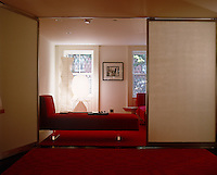 A  collection of Noguchi paper lamps glow in the window a New York living room where the room itself is contained by a system of sliding screens
