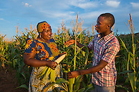 BRAC PROJECT, women farming maize in Dodoma, Kikuyu District. Sophia Mwidimya (in turban) farmer.  Lucas Florian, project manager discussing corn production with women.
