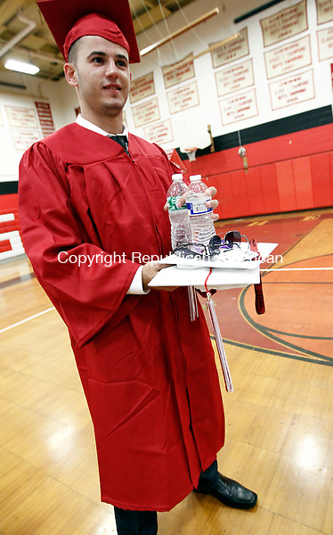 Cheshire, CT- 24 June 2014-062414CM01- Cheshire High School graduate Blendi Gashi balances water bottles, caps and glasses before the start of commencement exercises at the high school in Cheshire on Tuesday.  Christopher Massa Republican-American