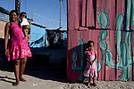 Khayelitsha, South Africa March 5, 2013: An unidentified family living next to Amandla EduFootball program. It was founded by Jakob Schlichtig, Florian Zech outside the field in Khayelitsha a poor township outside Cape Town, South Africa. They use football to initiate, support educational projects for youth in the township. The program keep children busy and it decreases the risk of them joining gang, criminal activity or teenage pregnancy. The crime level has decreased substantially in the area since the program was created in 2006. (Photo by: Per-Anders Petterssonl)