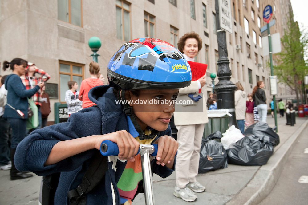 Marilyn Berger (C, middleground), widow of Don Hewitt, looks over at Danny Hodes (C, foreground), the 8 year-old Ethiopian she has taken in, as he waits on his scooter for the traffic light to change on the way back from school in New York, NY, USA, 9 April 2010. Ms Berger met him in Addis Ababa while reporting there and helped him get surgery.