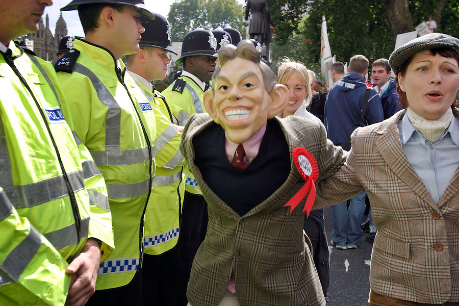 London, England, 15/09/2004..An estimated 20,000 hunt supporters demonstrate in Parliament Square as a new bill to ban hunting with dogs is passed. Some demonstrators fought with riot police, and five hunt supporters managed to get onto the House of Commons floor during the debate..A demonstrator in a Tony Blair mask runs past police.