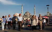 View from the front of Pedestrians walking in Eminonu, Istanbul, Turkey with The New Mosque or Mosque of the Valide Sultan (Yeni Cami, Yeni Valide Camii) in the background. Picture by Manuel Cohen.