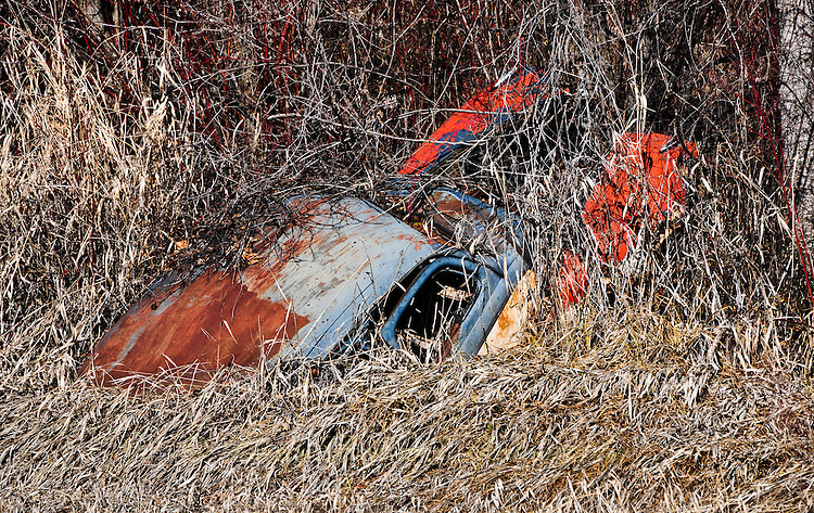 Old abandoned car stuck on the grassy banks of the Tobacco River in Montana