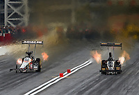 Mar 29, 2014; Las Vegas, NV, USA; NHRA top fuel dragster driver Terry McMillen (left) races alongside Troy Buff during qualifying for the Summitracing.com Nationals at The Strip at Las Vegas Motor Speedway. Mandatory Credit: Mark J. Rebilas-USA TODAY Sports