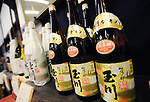 Bottles of high grade sake are lined up on the shelves of a store inside Tamagawa sake brewery in Kyoto, Japan. More than 1,200 sake breweries exist in Japan, though falling domestic consumption has lead some to look to  overseas markets. Photographer: Robert Gilhooly