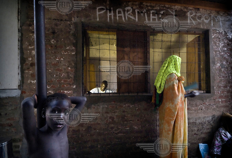A woman receives her prescribed medication from a pharmacy outside an MSF (Medecins Sans Frontieres) health clinic.