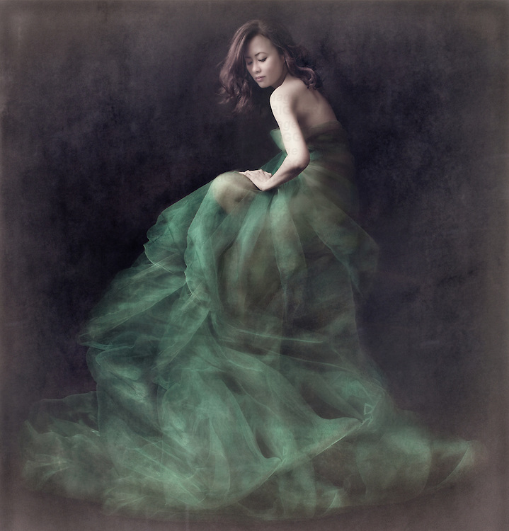 Young asian female with long dark hair sitting alone covered in green fabric