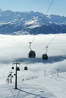"Switzerland. Valais. Crans Montana. Winter ski resort. CMA ( Crans Montana Aminona) blue cable cars and ski lifts are carrying people to the top of the mountain, while other are skiing down  the ""Pas du loup"" slopes on a sunny day with blue sky. The fog is covering the Rhone valley. © 2005 Didier Ruef"