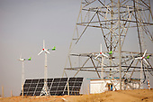 China is investing heavily in renewable energy projects such as these solar panels and wind powered electric power next to a cell phone tower in a remote part of Inner Mongolia.