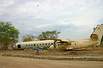 Two crashed planes lie by the side of the main road running through Rumbek, South Sudan, vestiges of generations of civil war.