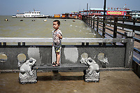 A young boy escapes the flooding near Dongting Lake, Hunan Province. Dongting Lake has decreased in size in recent decades as a result of land reclamation and damming of the Yangtze. China. 2010