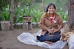 Jovita Guzman, a Maya Mam woman, pulls the grain off of corn at her home in Comitancillo, Guatemala.