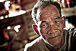 Bon Oum Von, a 59 year-old plantation worker, at his un-powered, un-plummed home outside of Koh Kong, Cambodian. Von facilitated migrant crossings from 1991-2002; at times the migrants were so poor he wouldn't charge the approximately $3 USD fee for his help navigating the land mine riddled border crossing. The non-governmental organization Legal Support for Children and Women works with several partners to to help undocumented migrants hwo are often exploitate by smugglers, employers, border police, and immigration officials on both sides ofthe border.