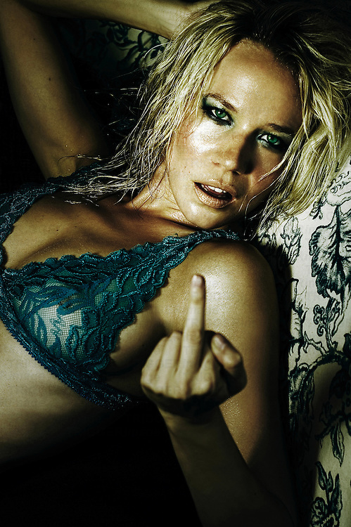 A young woman with blonde hair giving the middle finger