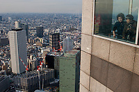 Two older women look out a window on the 45th floor observation deck of the Tokyo Metropolitan Government building. Shinjuku, Tokyo, Japan. Wednesday, January 7th 2009