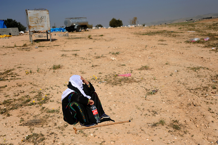 ISRAEL El-Arakib, Negev desert<br /> A woman sits aside on the ground.<br /> <br /> The unrecognized Bedouin village of El-Arakib, in Israel's southern Negev desert, is at the center of land dispute between Bedouin residents and Israel's government. Its residents were allowed to reside in the cemetery compound of the village, and as of March 2011, structures outside the compound were demolished by authorities for the 21st time already.