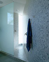 The sunlight pouring in from the vertical slit window gives a sense of infinity to this angular shower room