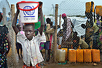 A girl carries water from a communal water point inside a camp for internally displaced families located inside a United Nations base in Juba, South Sudan. The camp holds Nuer families who took refuge there in December 2013 after a political dispute within the country's ruling party quickly fractured the young nation along ethnic and tribal lines. The ACT Alliance is providing a variety of services, including fresh water, sanitation and refuse collection services, to the more than 20,000 people living in the camp.