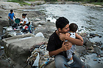 November 07, 2014. &quot;Water it&acute;s the real thing&quot;<br /> Edwin Salguero with his son Edwin in Acelhuate river (Nejapa, El Salvador). He does&rsquo; t have drinking water at home. The river is contaminated. Edwin and his family have to walk near two hours to get the river. <br /> The people of Nejapa in El Salvador, have no drinking water because the Coca -Cola company overexploited the aquifer in the area, the most important source of water in this Central American country. This means that the population has to walk for hours to get water from wells and rivers. The problem is that these rivers and wells are contaminated by discharges that makes Coca- Cola and other factories that are installed in the area. The problem can increase: Coca Cola company has expansion plans, something that communities and NGOs want to stop. To make a liter of Coca Cola are needed 2,4 liters of water. &copy;Calamar2/ Pedro ARMESTRE