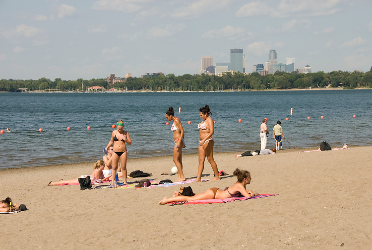 Minnesota, Twin Cities, Minneapolis-Saint Paul: Recreation at the south end of Lake Calhoun, with the Minneapolis skyline in the background.  Women beach bathers..Photo mnqual274-75197..Photo copyright Lee Foster, www.fostertravel.com, 510-549-2202, lee@fostertravel.com.