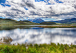 White clouds are reflected in the clear blue water of Wideon Pond at Red Rock Refuge in Montana.