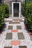 Entrance to house made more appealing with simple flagstone and pebble path and tier of plants and shrubs allee