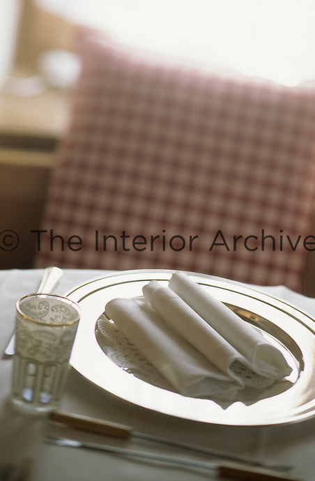 A silver plate with an elegantly folded white napkin flanked by an antique gold rimmed glass