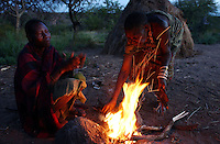 Yaeda Valley, Tanzania: Veronique, left, and an older Hadzabe woman, right, roast roots gathered earlier in the day over a fire in this settlement of straw huts in Northern Tanzania. The Hadzabe are one of the last tribes of hunter gatherers on earth, and the second oldest people in human history, with a culture dating back at least 60,000 years. They live on a diet of roots, herbs, honey they gather, and wild animals they hunt. There are currently fewer than 1,500 Hadzabe left. (PHOTO: MIGUEL JUAREZ LUGO)