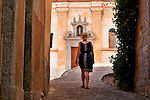 A woman wearing a straw hat walks towards the church in Nesso, a town on Lake Como, Italy