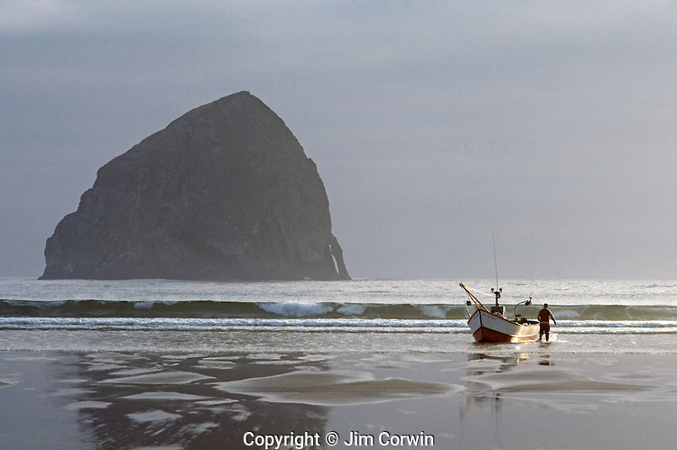 Dory along shoreline with storm clouds getting ready to launch at sunrise for fishing Cape Kiwanda State Park National Recreation Area near Pacific City northern Oregon coast Oregon State USA .