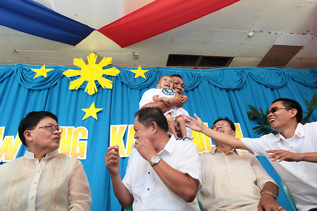 Eighteen-year-old Junrey Balawing, the world's shortest living man, is hoisted up by local officials during annual Independence Day celebrations in the town of Sindangan, Mindanao island, Philippines. June 12, 2011.