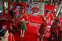 """Girls wearing traditional clothes display a picture of ousted premier Thaksin Shinawatra during a religious ceremony at a temple in the village of Suan Mon near Udon Thani in northeastern Thailand June 25, 2011. Regional leaders of Thailand's red-shirt protest movement held traditional Buddhist ceremony to launch 38 villages designated as """"Red Shirt Village of Democracy."""" The red shirts, supporters of ousted premier Thaksin Shinawatra, have been branding hundreds of villages as red to rally behind Thaksin's sister, Yingluck, who is leading the opposition ahead of July 3 general elections.   REUTERS/Damir Sagolj (THAILAND)"""